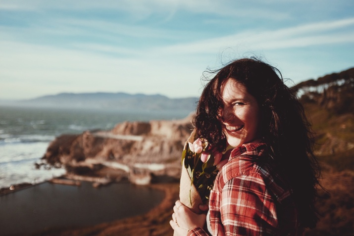 woman standing on a cliff area looking back smiling with flowers in her hands